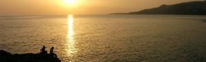 Dos personas mirando la puesta del sol junto al mar en España